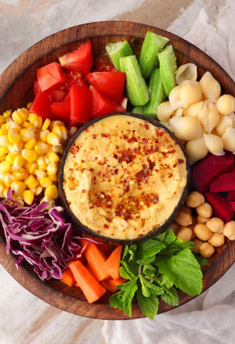 Mediterranean Rainbow Bowl with hummus in a wooden bowl