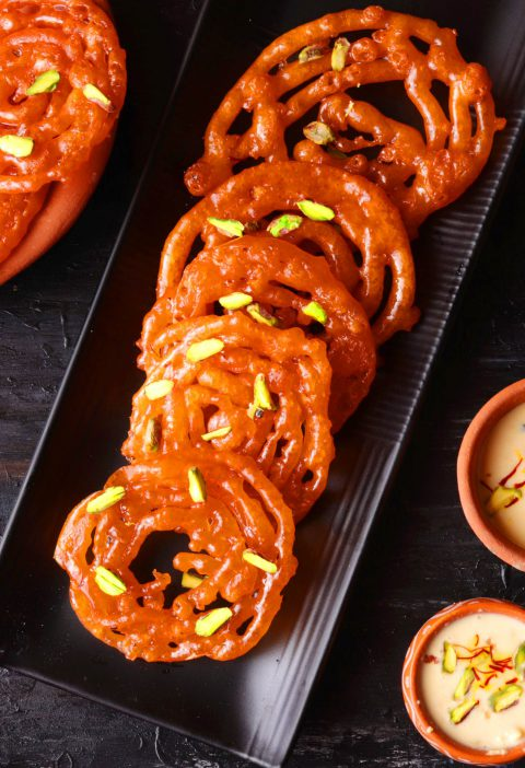Jalebis on a black tray over a black table with kesar rabri on the side