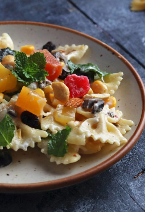 Fruit and nut Pasta Salad on a white cermaic plate over a blue table