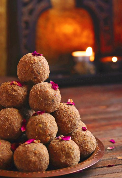 Protien rich laddus on a copper plate over a wooden table with candles burning in the vackground