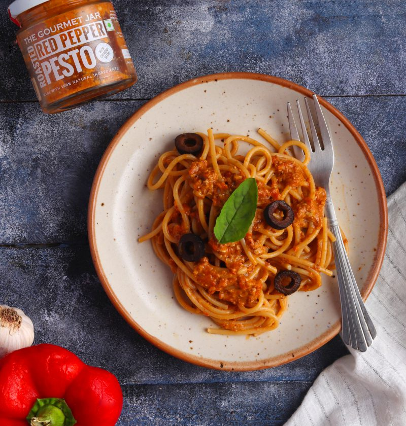 Red Pepper Pesto Spaghetti on a white plate over a blue table