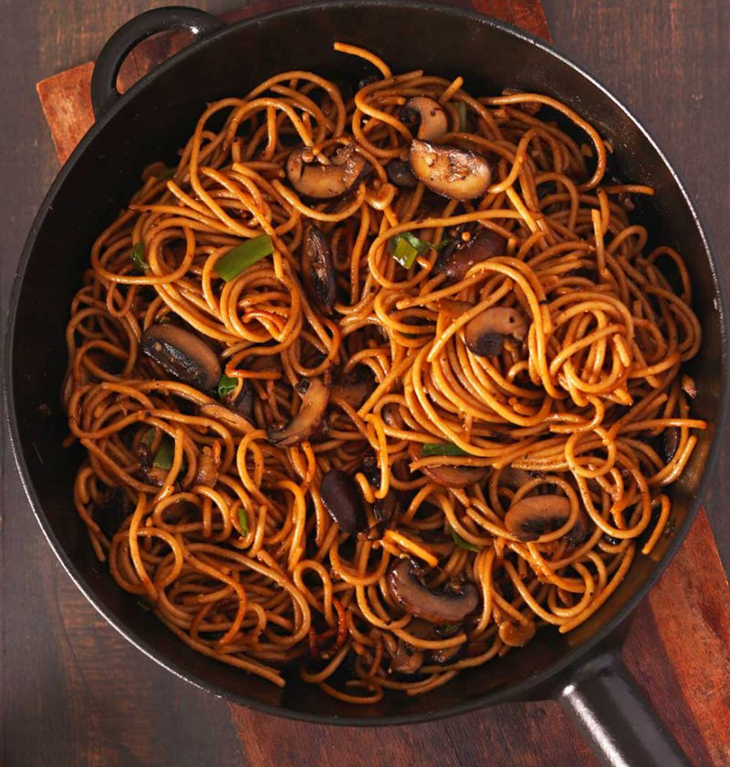 Garlic Mushroom Noodles in a black frying pan on a wooden table