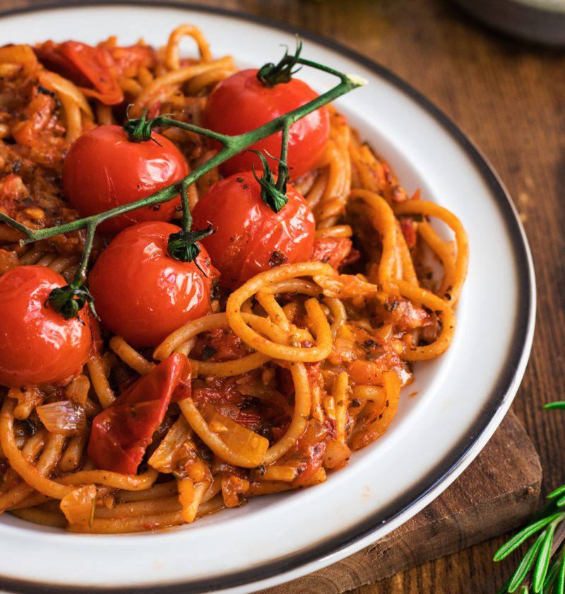 Roasted Cherry Tomatoes Pasta on a white plate over a wooden table