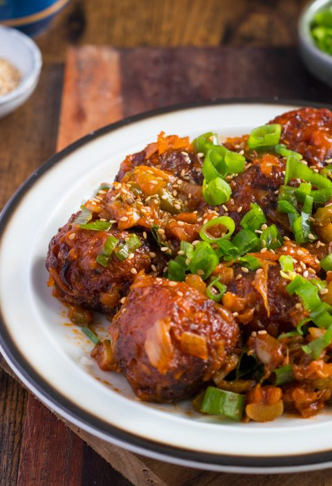 Dry Manchurian on a white plate planes on a wooden table