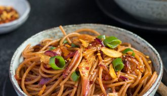 Chilli Garlic Noodles in a white ceramic bowl on a black textured table with another bowl of noodles in the background