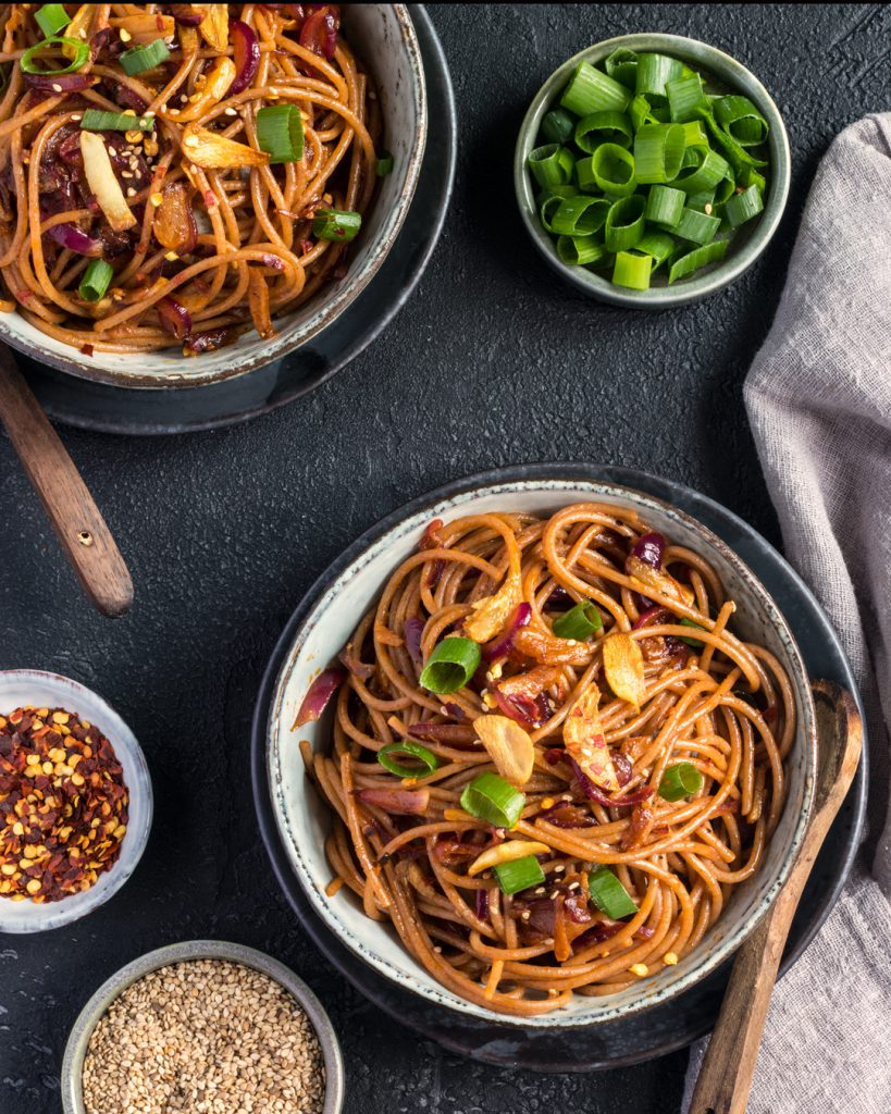 Two bowls of Chilli Garlic Noodles in a white ceramic bowl on a black textured table