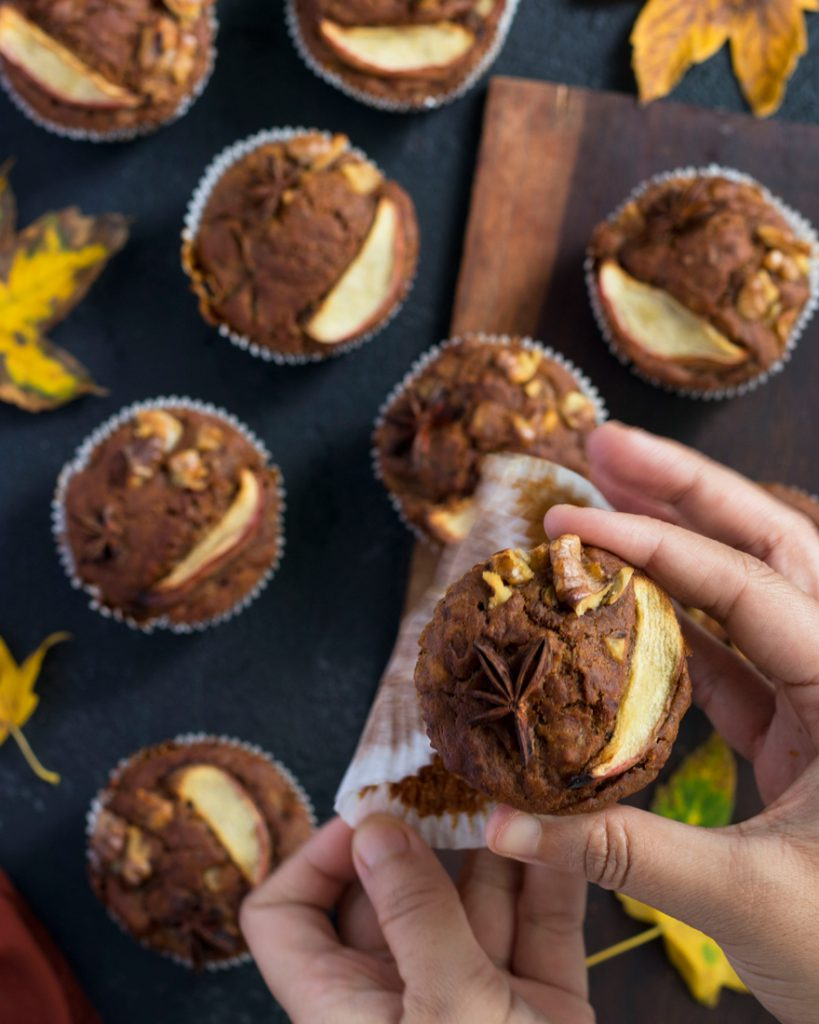 Eggless Apple Muffins over a black table with autumn leaves around them and a orange napkin