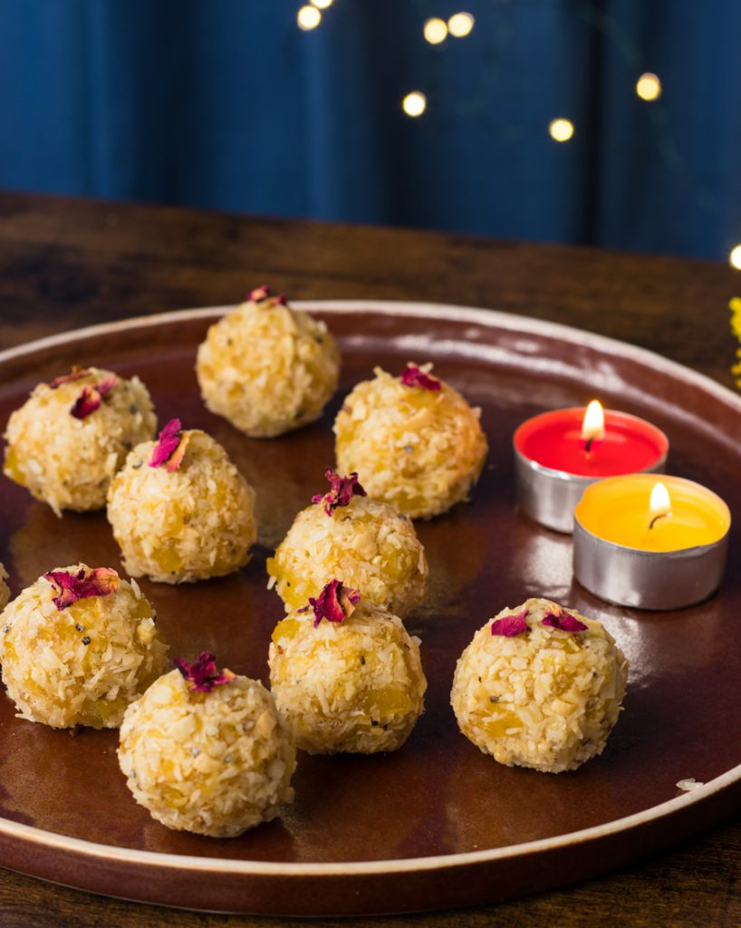 Vegan Pineaaple laddus on a copper coloured plate with yellow and red candles abd flowers