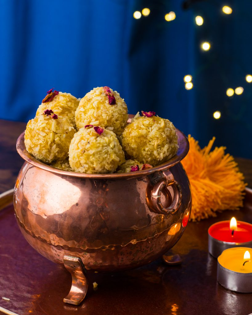 Vegan Pineaaple laddus on a copper containerplate with yellow and red candles and flowers